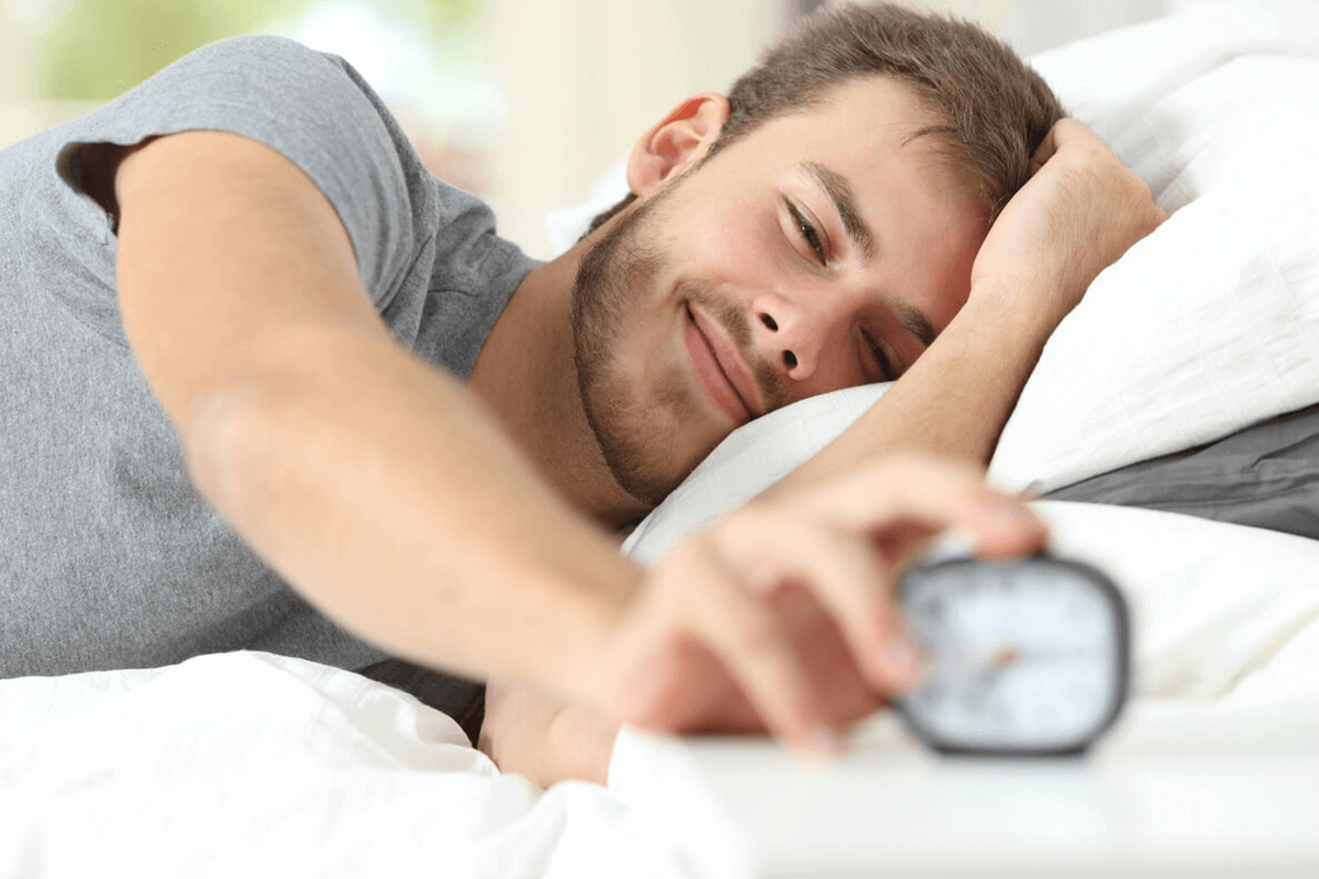 man in bed reaching out for his alarm clock