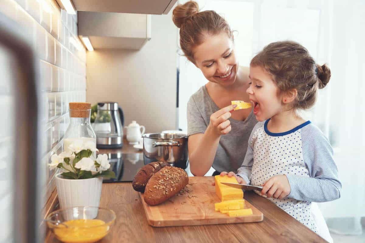 woman feeding her daughter cheese