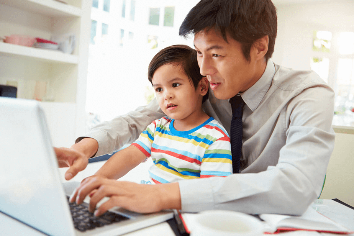 Father working on a computer with son