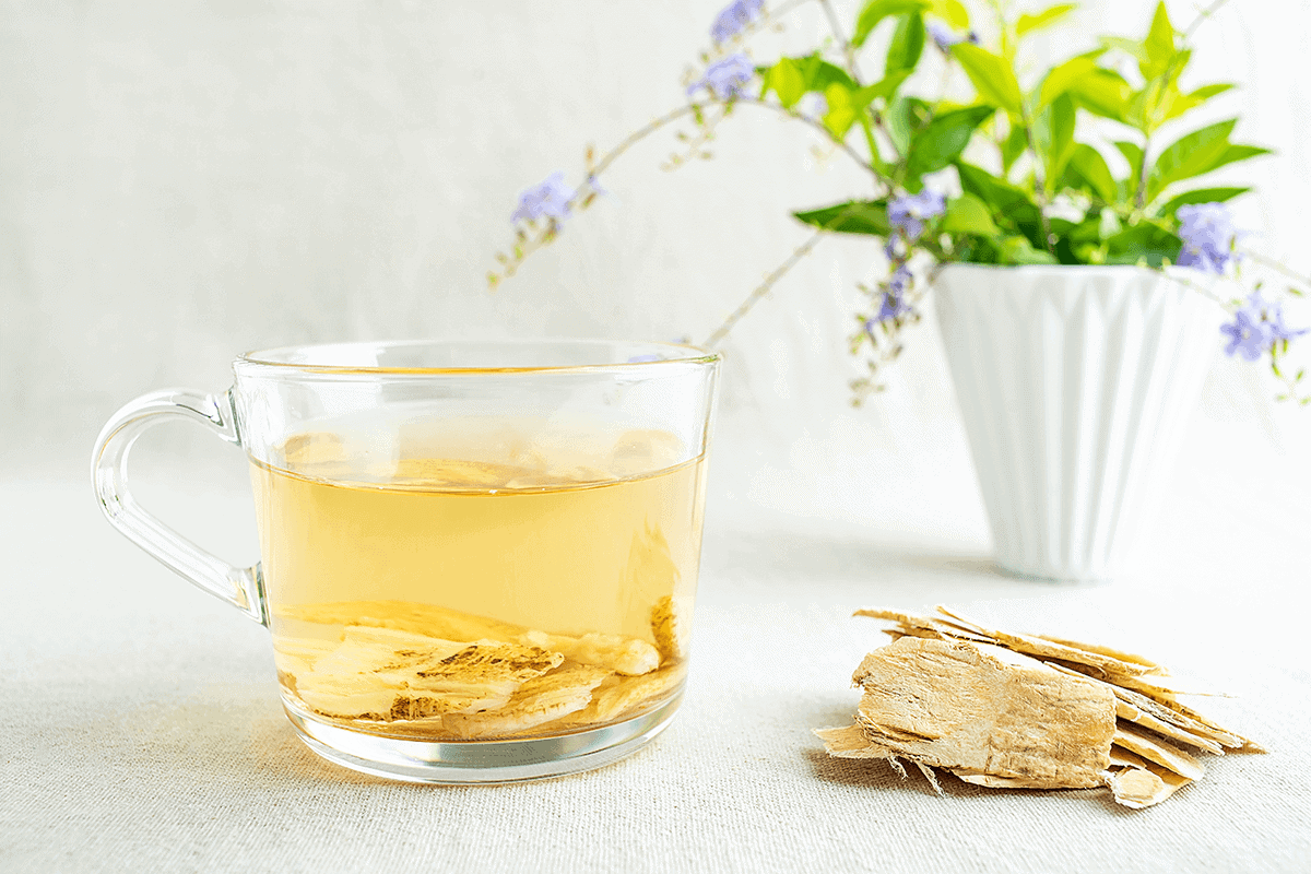 Astragalus extract in tea and next to the cup of tea