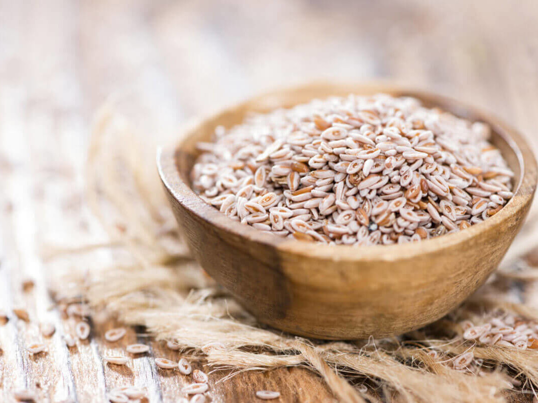 Psyllium seeds in a small bowl on a wooden table