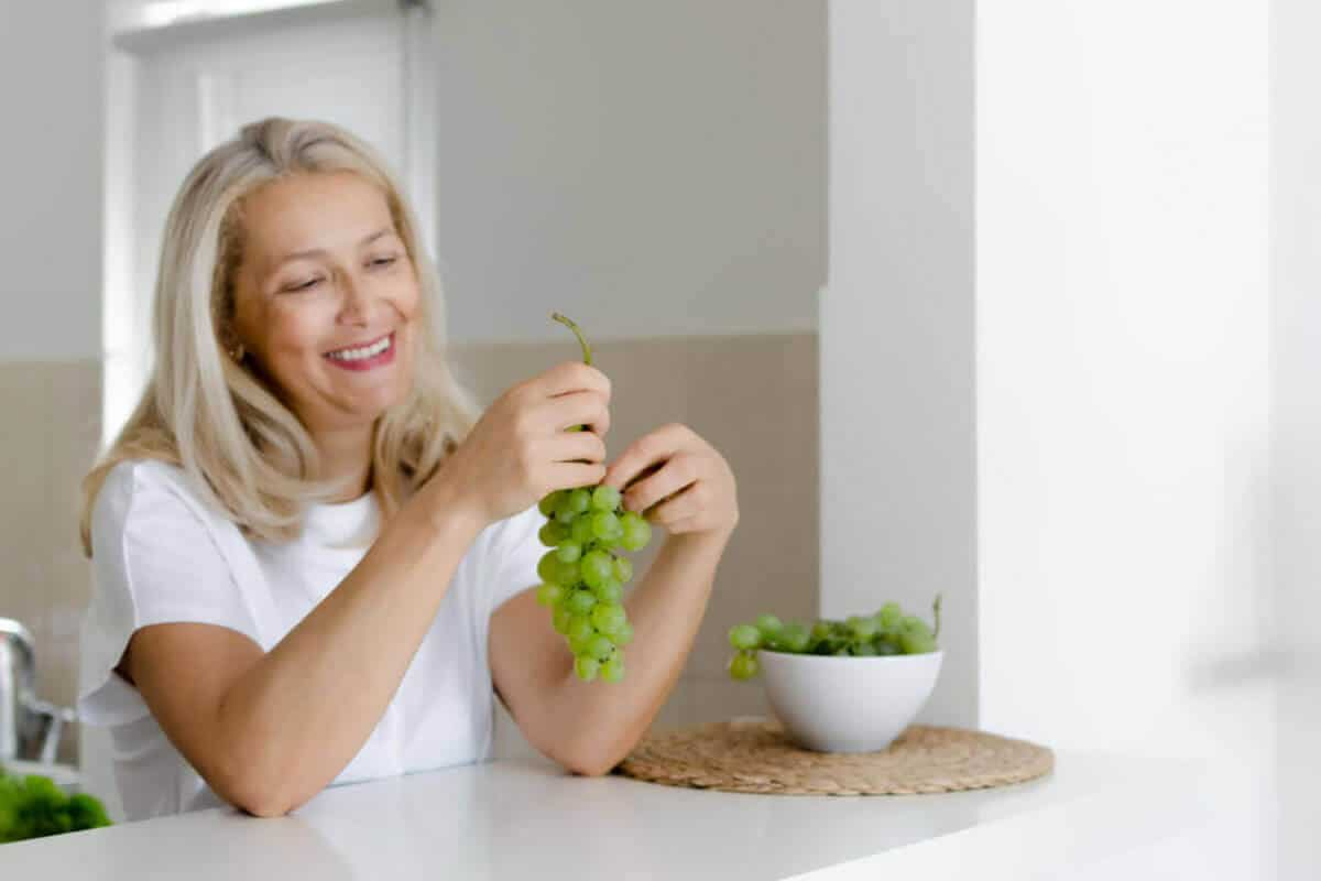 elder woman sitting in kitchen eating grapes