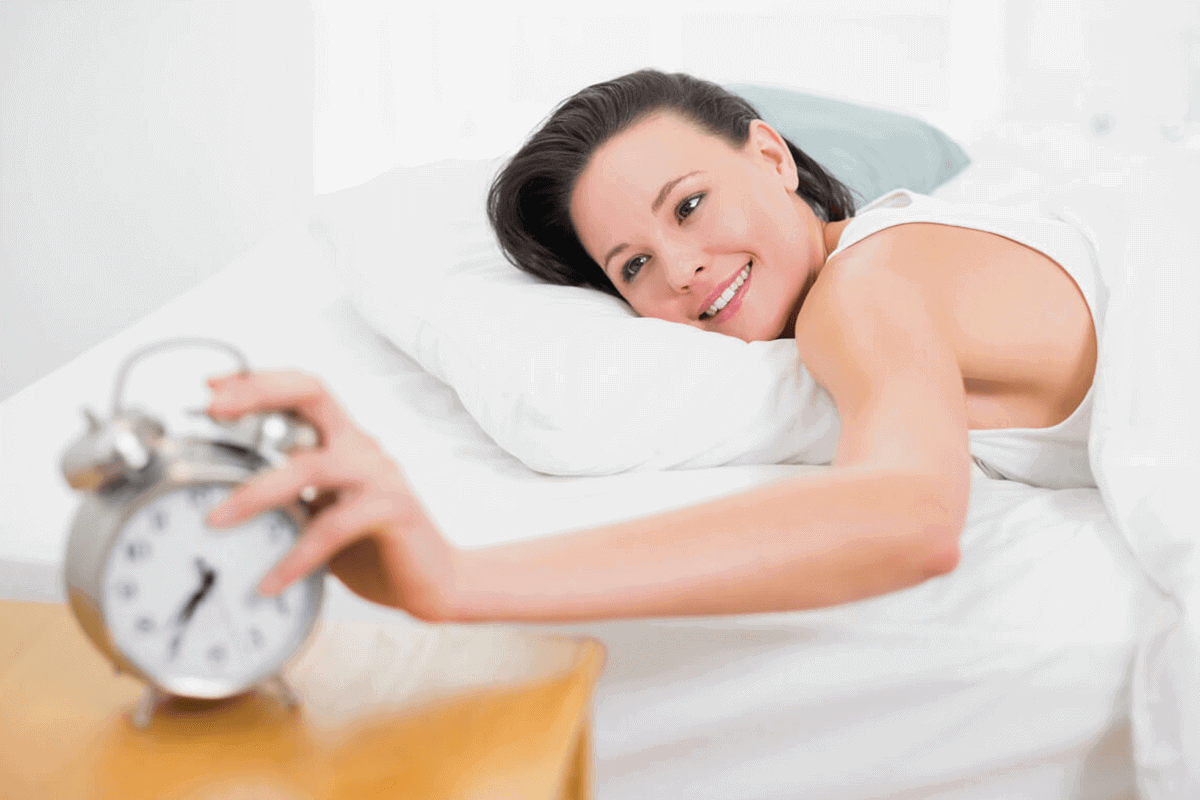 woman in bed hitting her alarm
