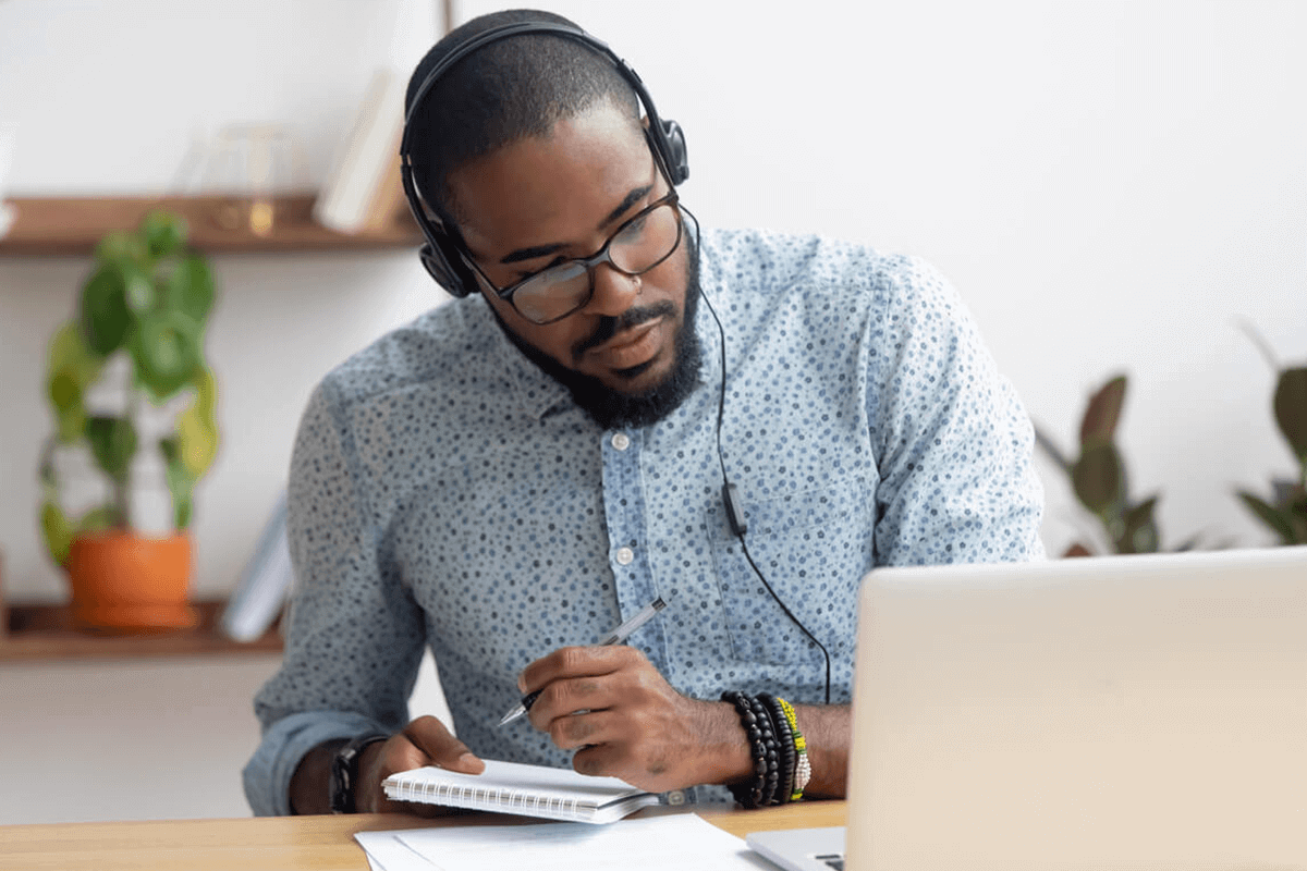 person with headphones taking notes and looking at their computer