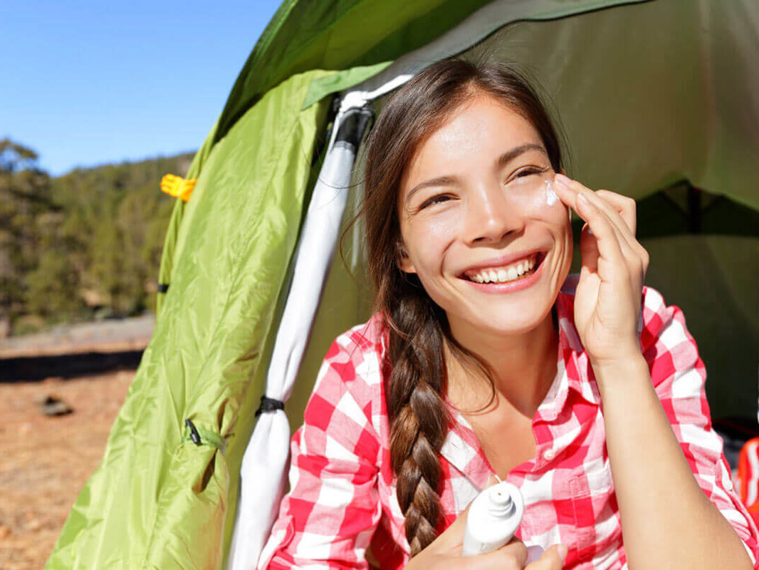 woman applying sunscreen on her face sitting in a tent
