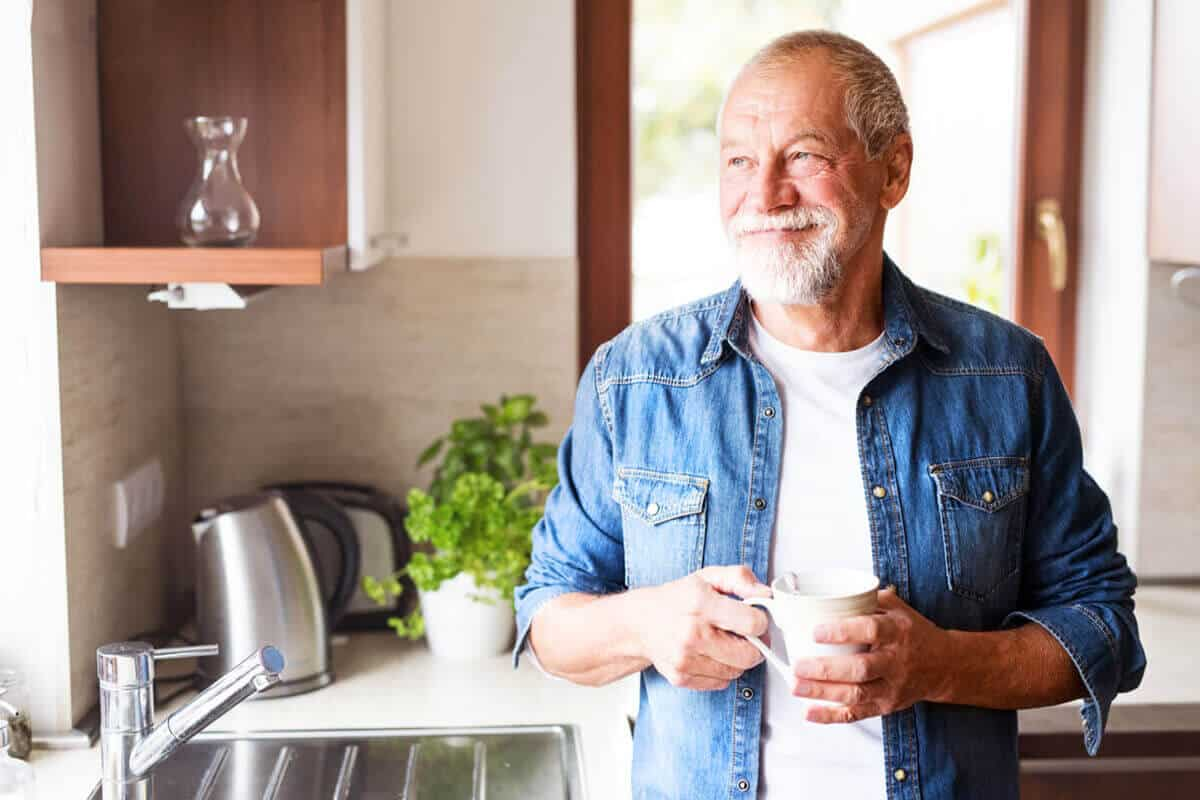older man standing in kitchen looking out the window and smiling holding a mug