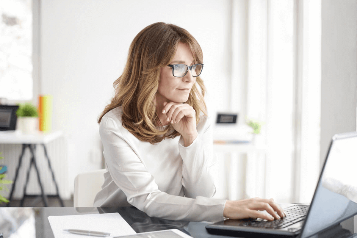 woman with reading glasses looking at her laptop