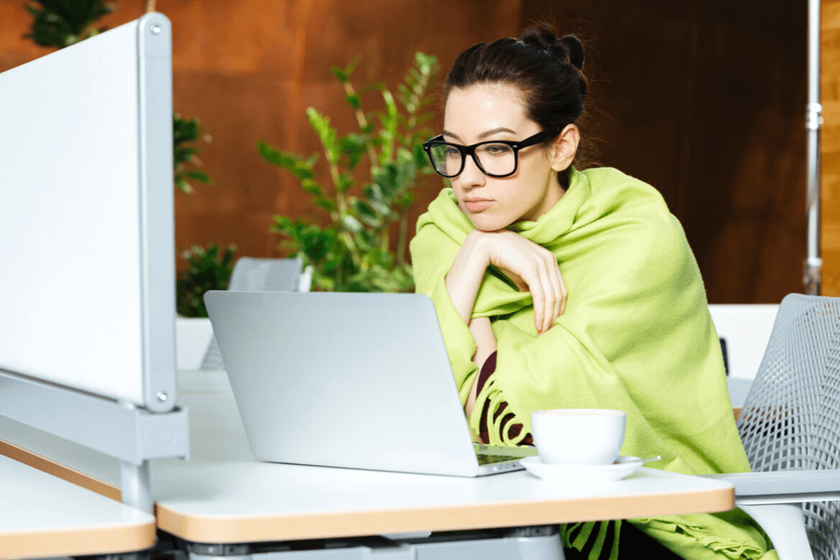 woman wrapped in a blanket looking at her laptop