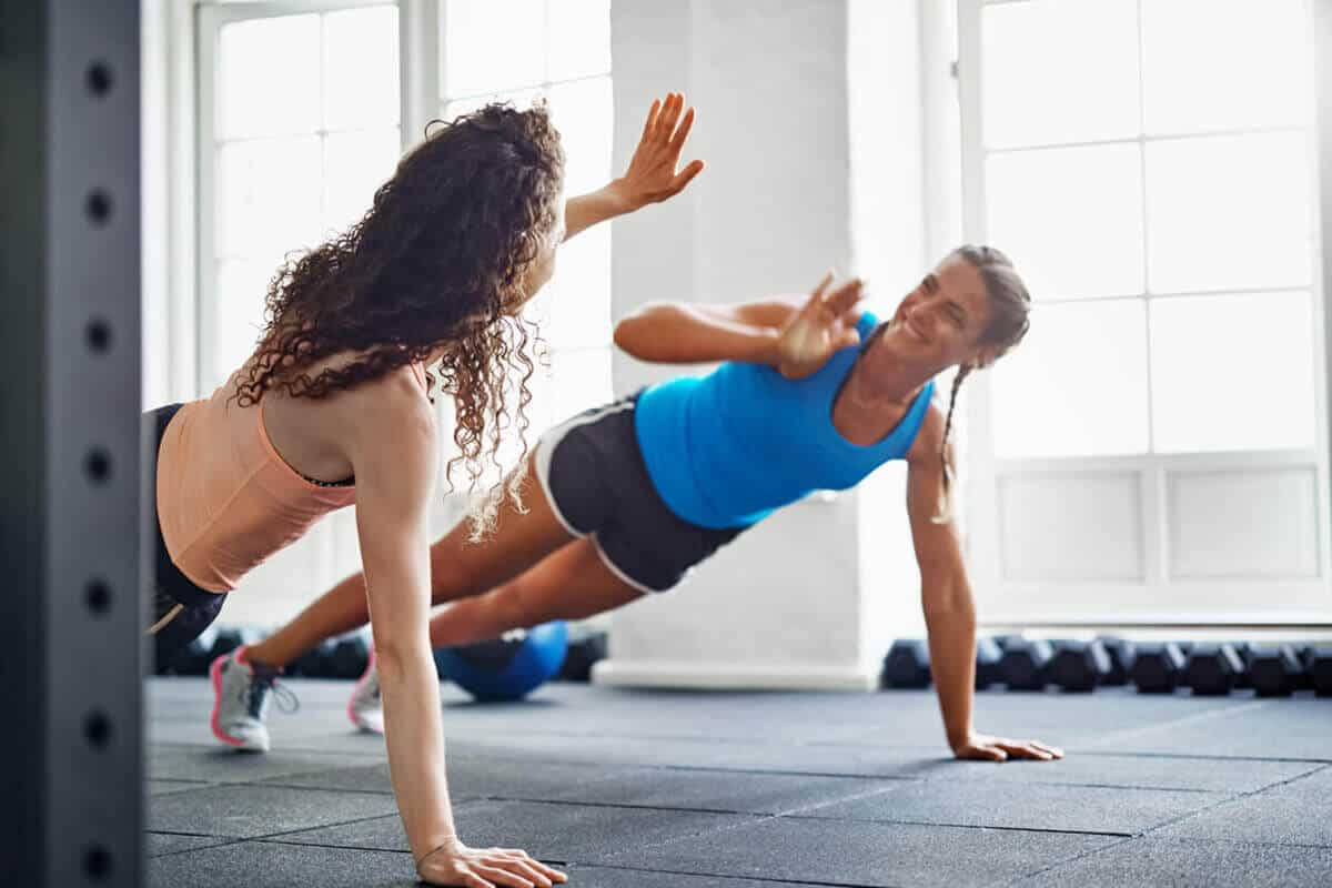 two women giving each other a high five while planking