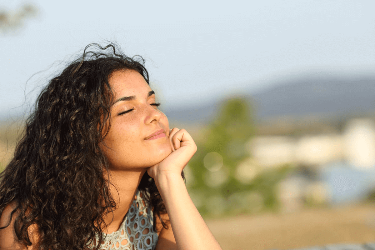 woman smiling with eyes closed in the sun