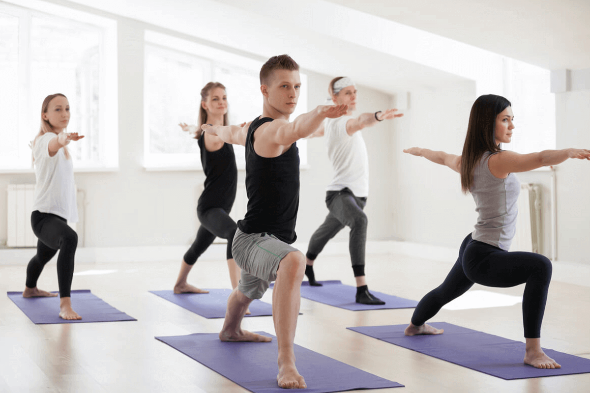 group of five people doing yoga together