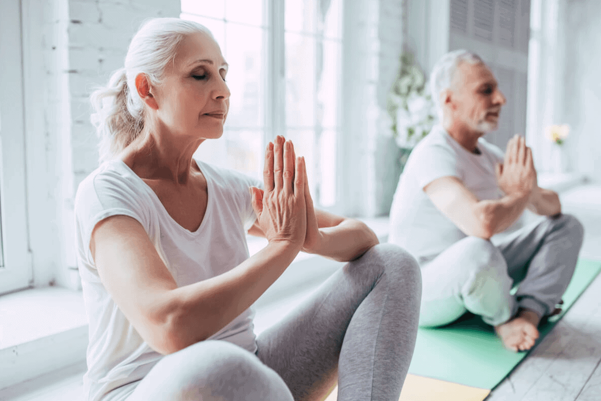 elder couple practicing yoga together