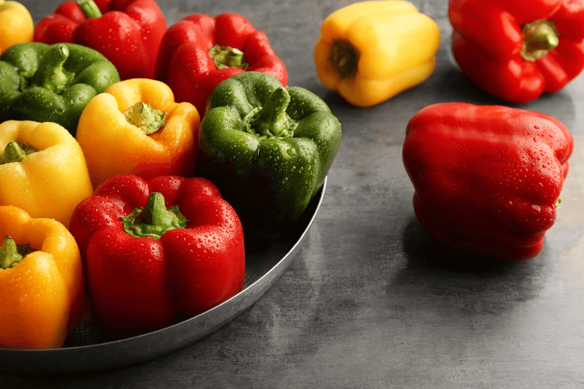 red, green, yellow peppers in a bowl all together