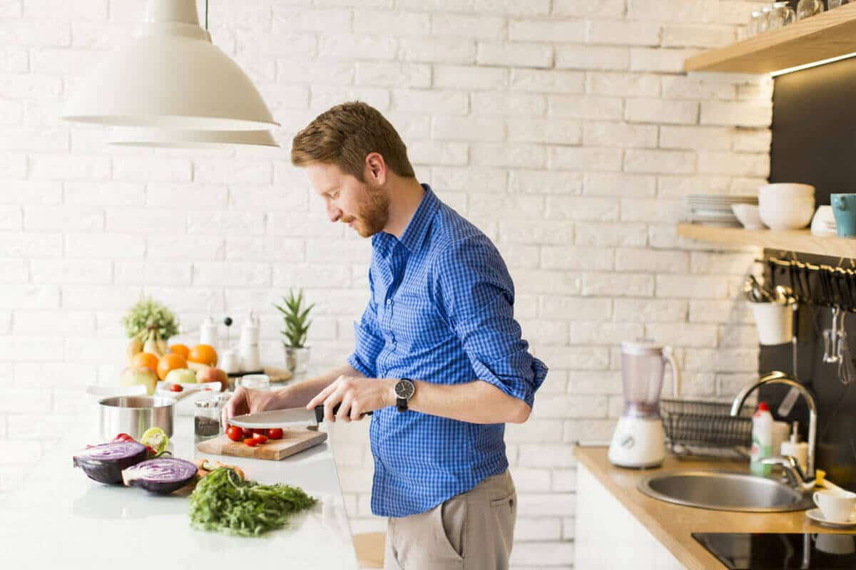 Man preparing food in a bright kitchen.