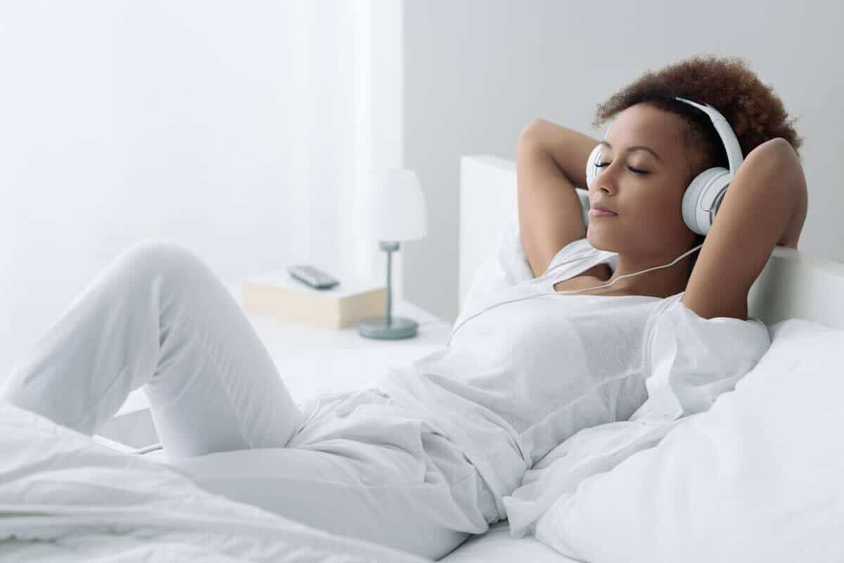 woman lying on her bed with headphones