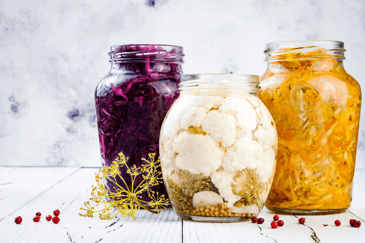 Jars of sauerkraut and pickled vegetables with herbs.