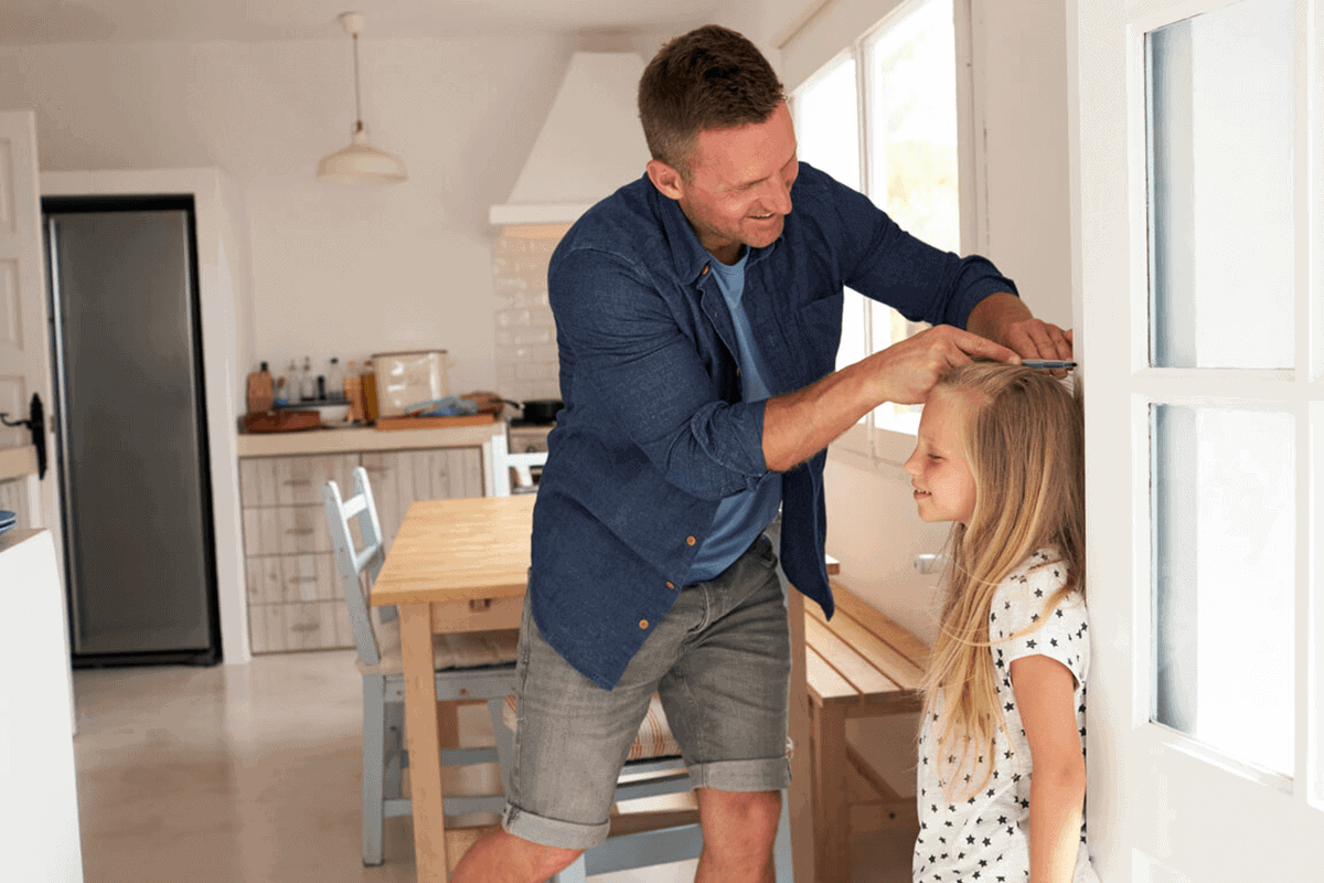 dad measuring daughter's height on wall