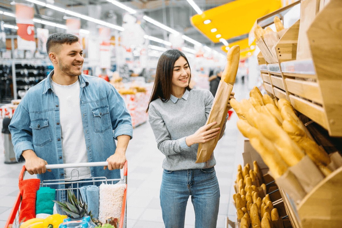 man and woman at the grocery store holding bread