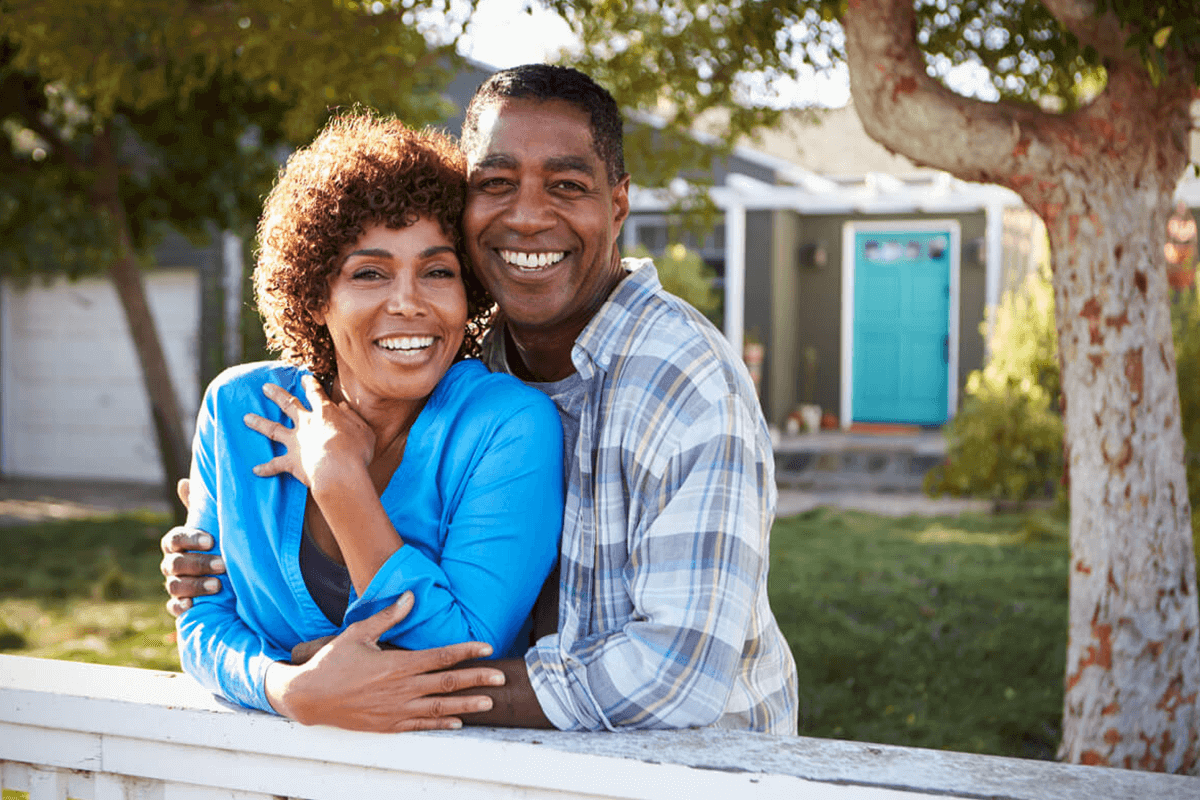 Mature couple looking over the fence in a front yard.