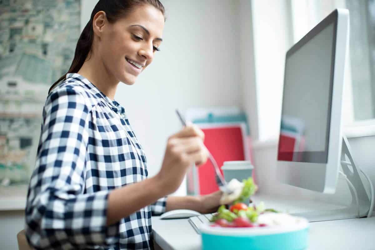 woman sitting at her desk and eating a salad