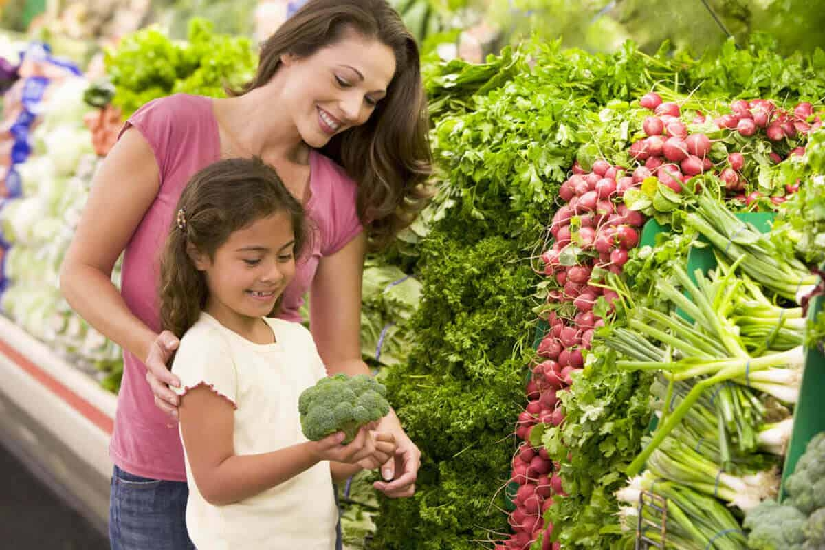 mother and daughter at grocery store picking up vegetable