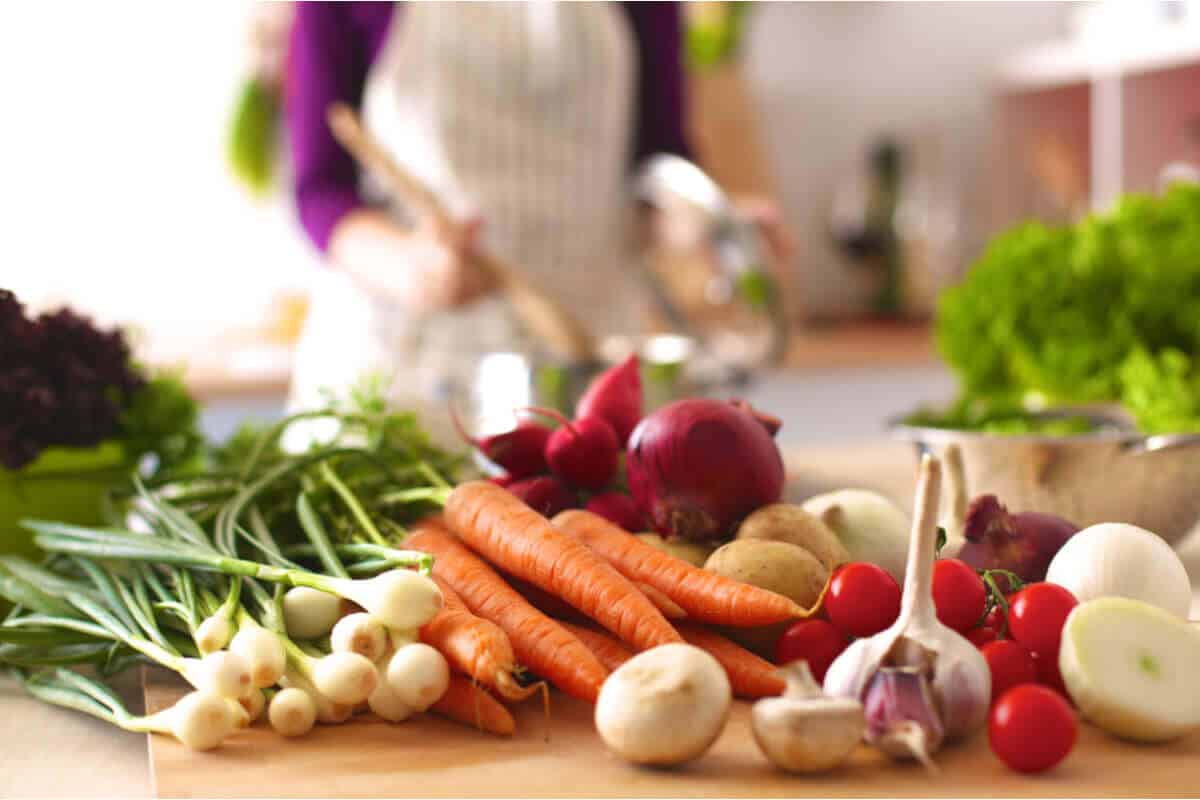 A young woman cooking in a kitchen with an assortment of colorful vegetables.