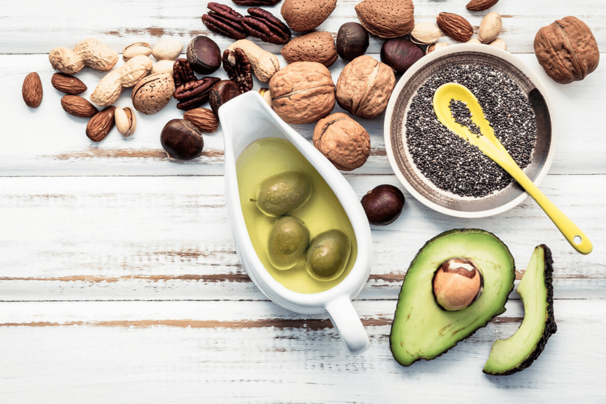 Flat-lay of nuts, avocado, olives in olive oil, and softgel capsules on a wooden table.