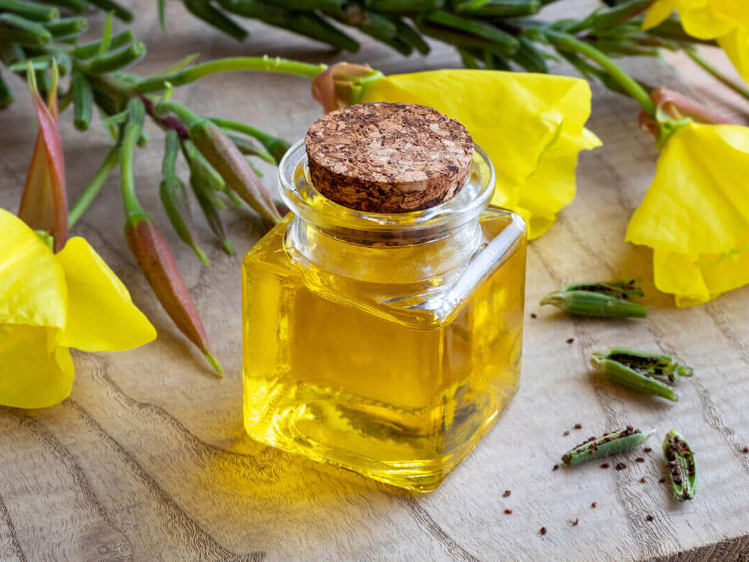 A bottle of evening primrose oil with flowers and seeds.