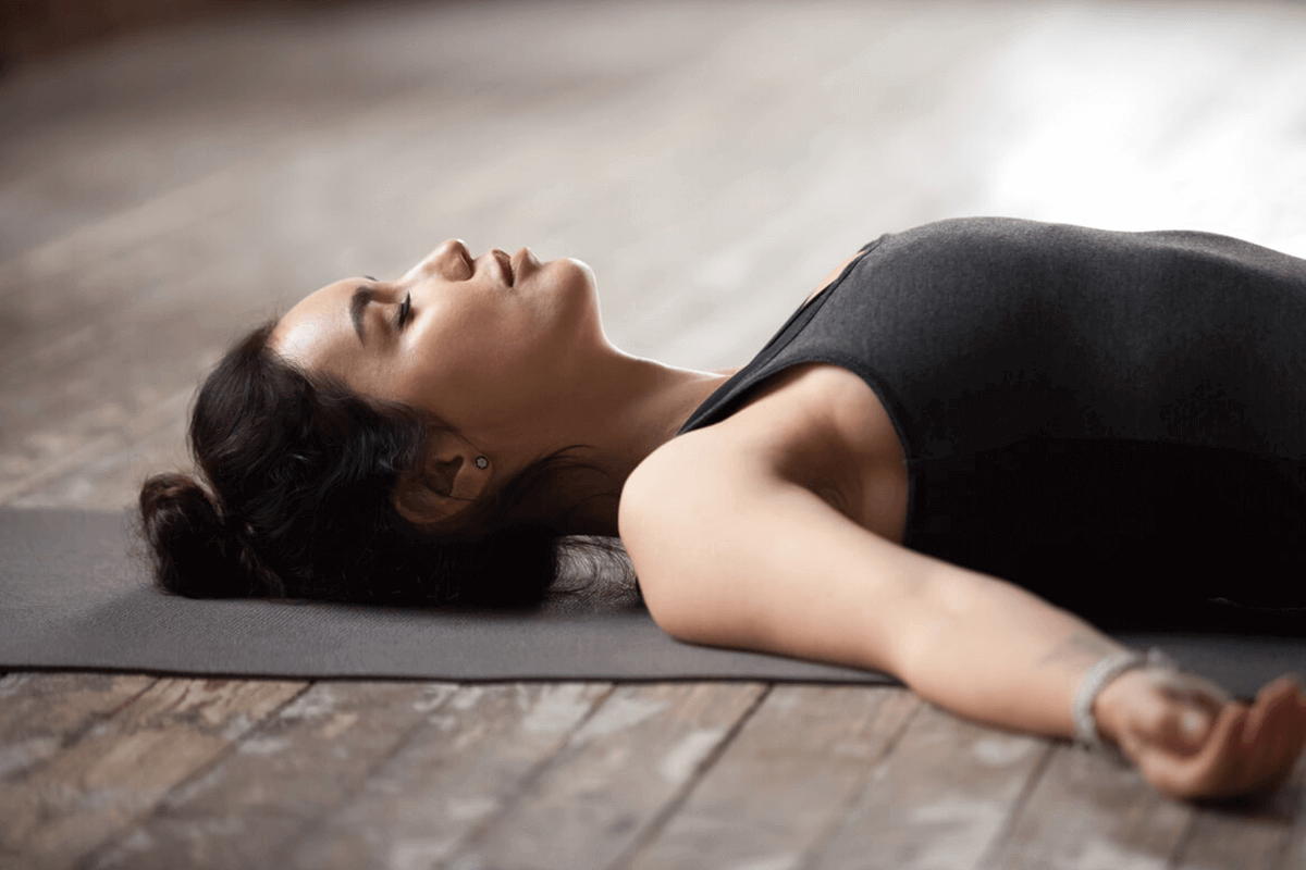 woman laying on yoga mat