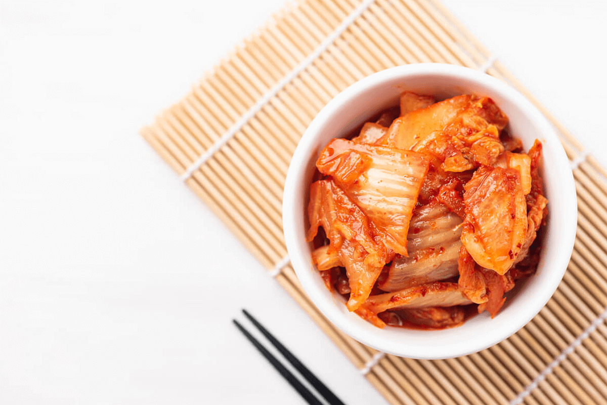 kimchi in a bowl with chopsticks