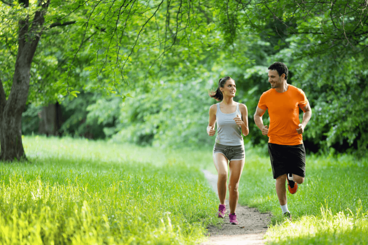Woman and man running through a park in the summer.
