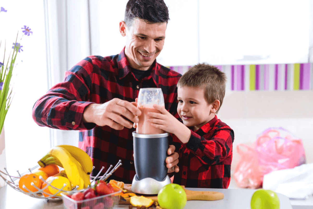 father and son making a smoothie in the kitchen