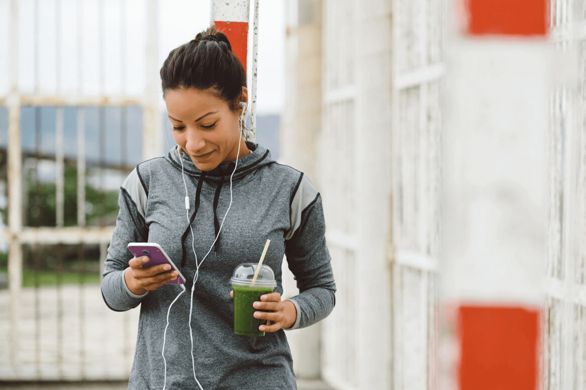 woman looking at phone with smoothie in hand in workout clothing