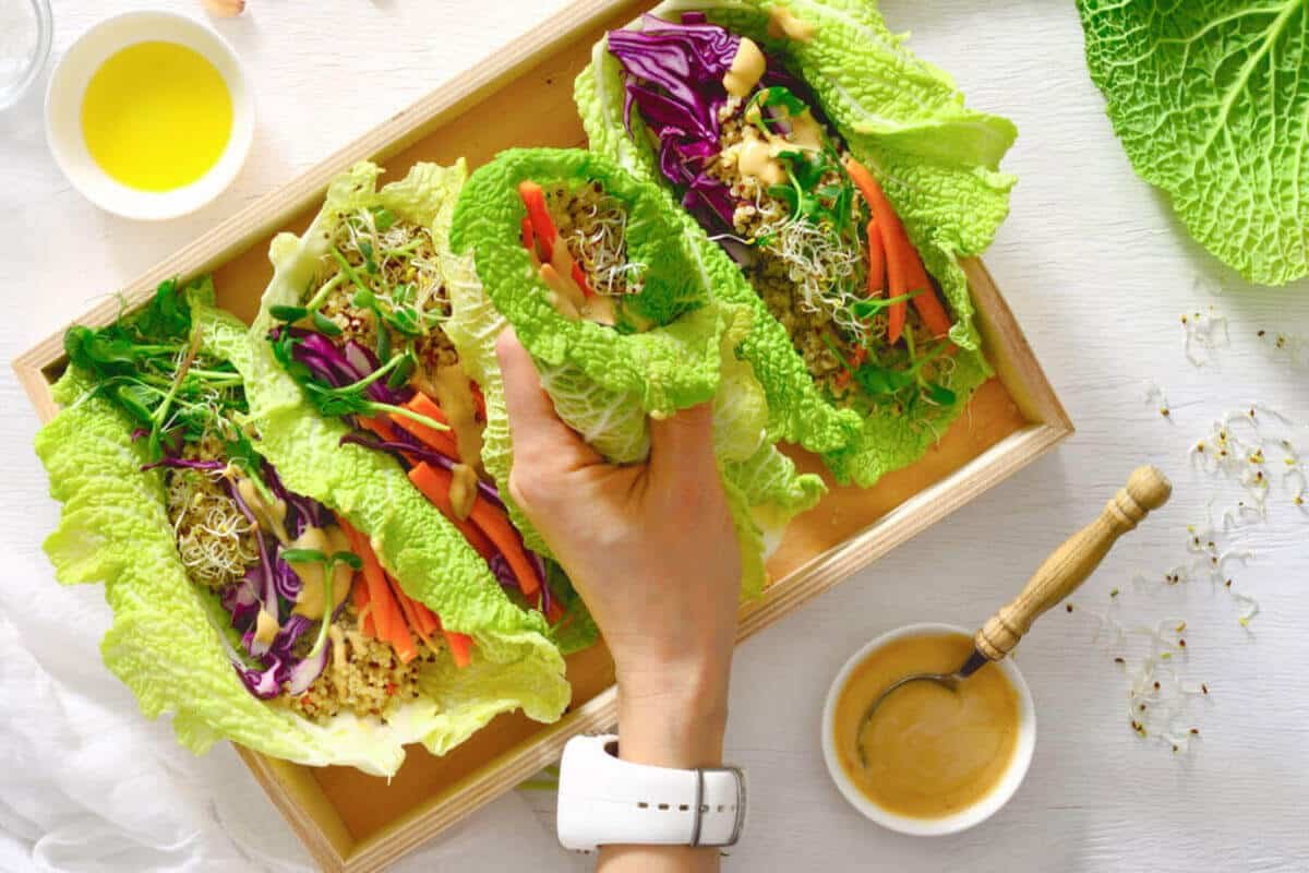 Colorful vegetarian lettuce leaf wraps on a white table.