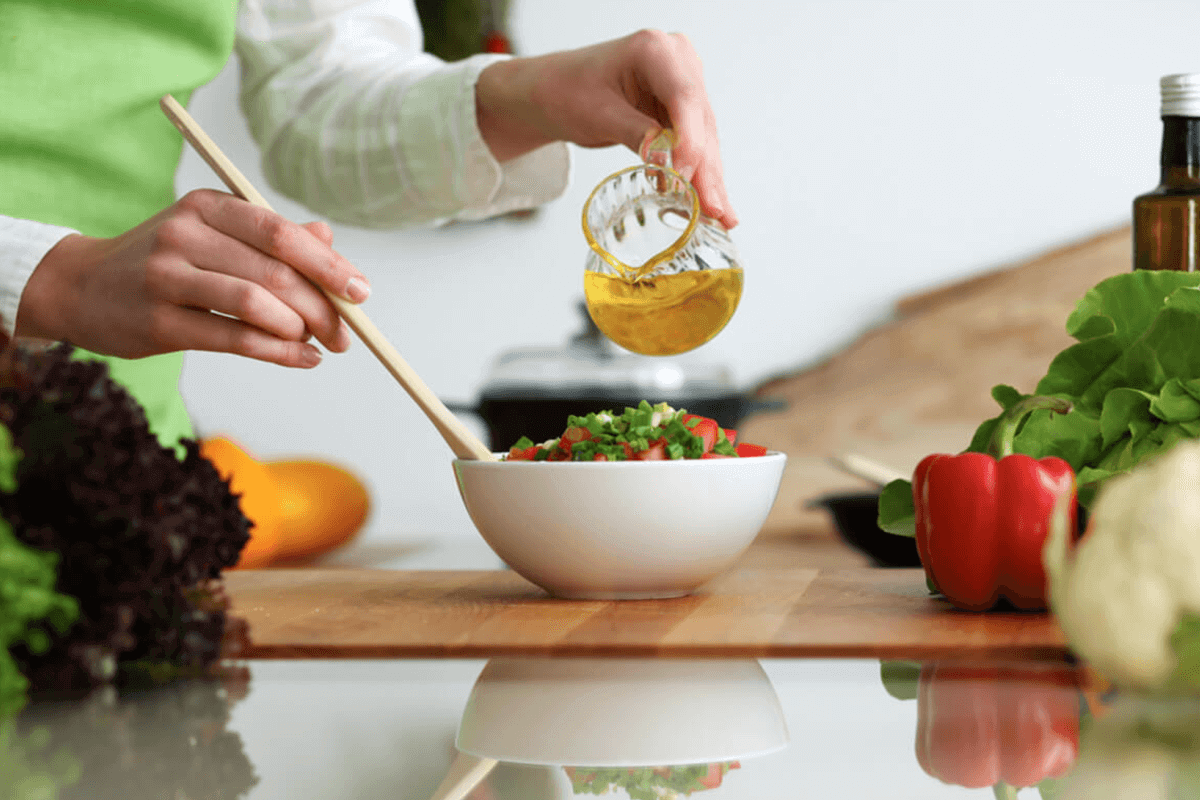 person pouring oil on a bowl of salad