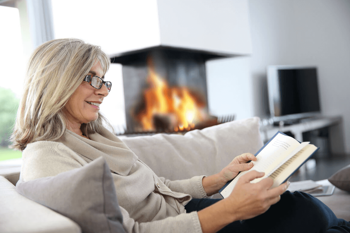 woman sitting on couch indoors reading a book