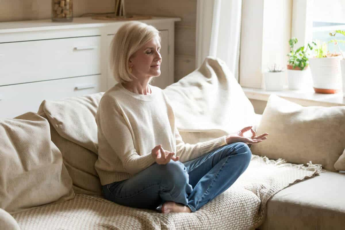 woman meditating on her couch in living room