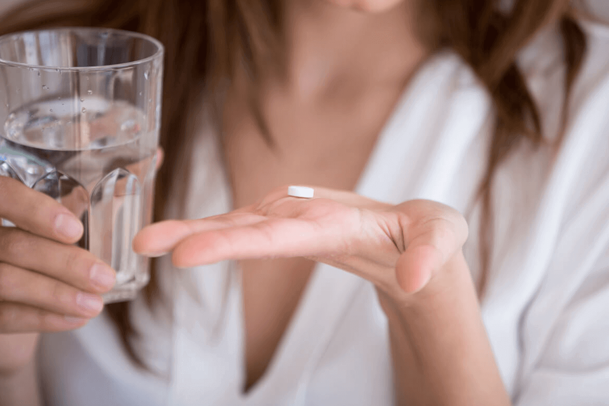 close up of woman's hand with supplement pill on it and water in the other hand