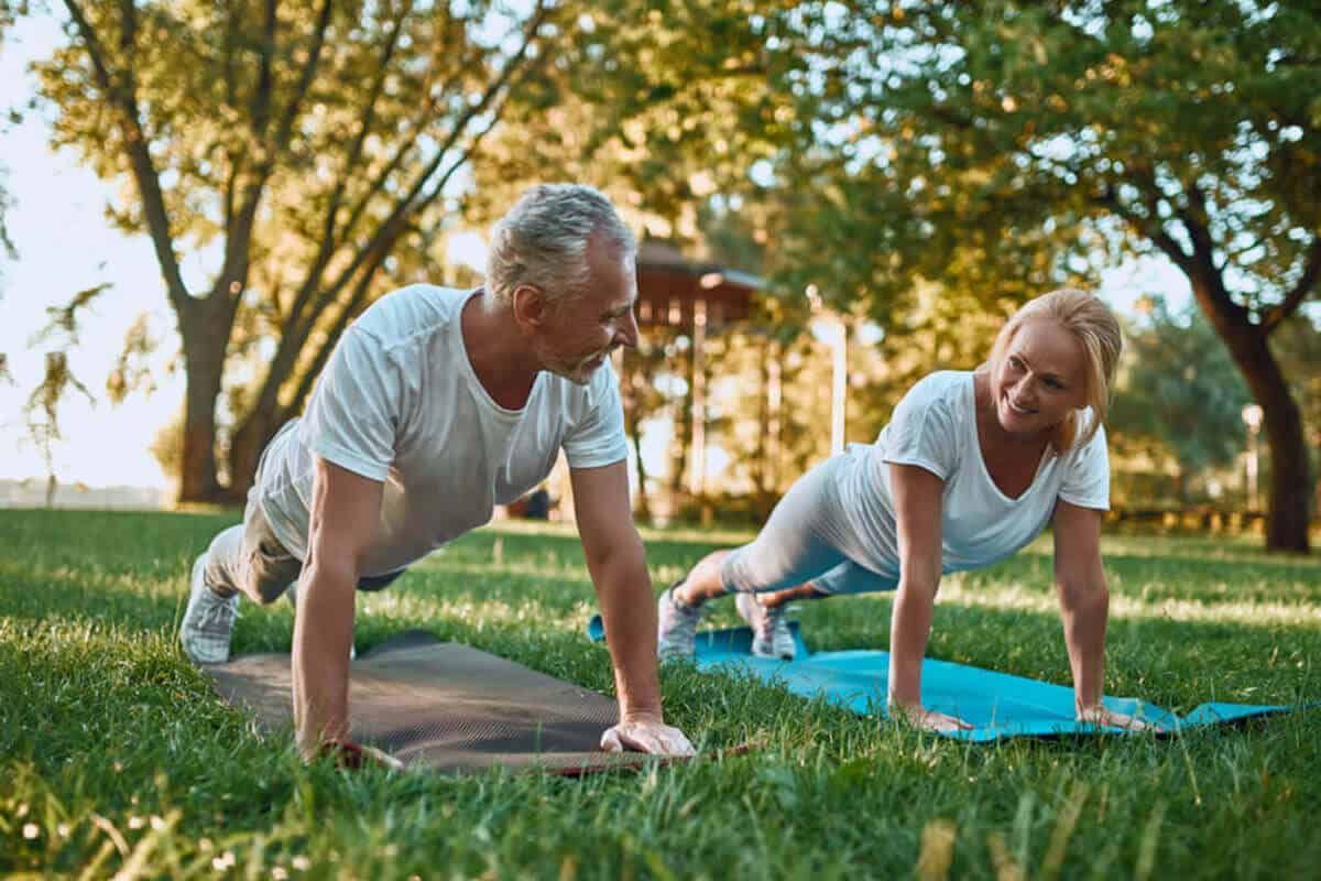 elder couple exercising outdoors on yoga matts