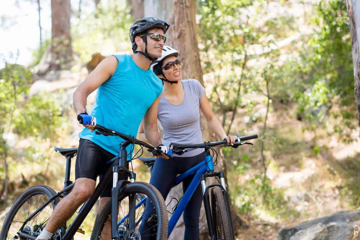 man and woman riding bikes in the woods