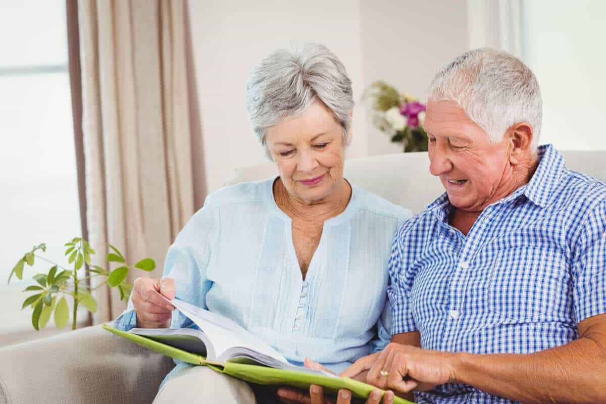 older couple sitting on couch reading a book