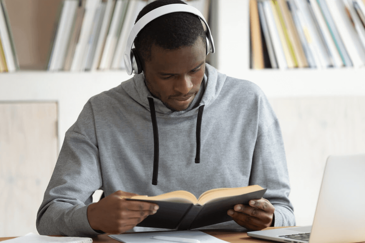 medical student with headphones on, reading a book