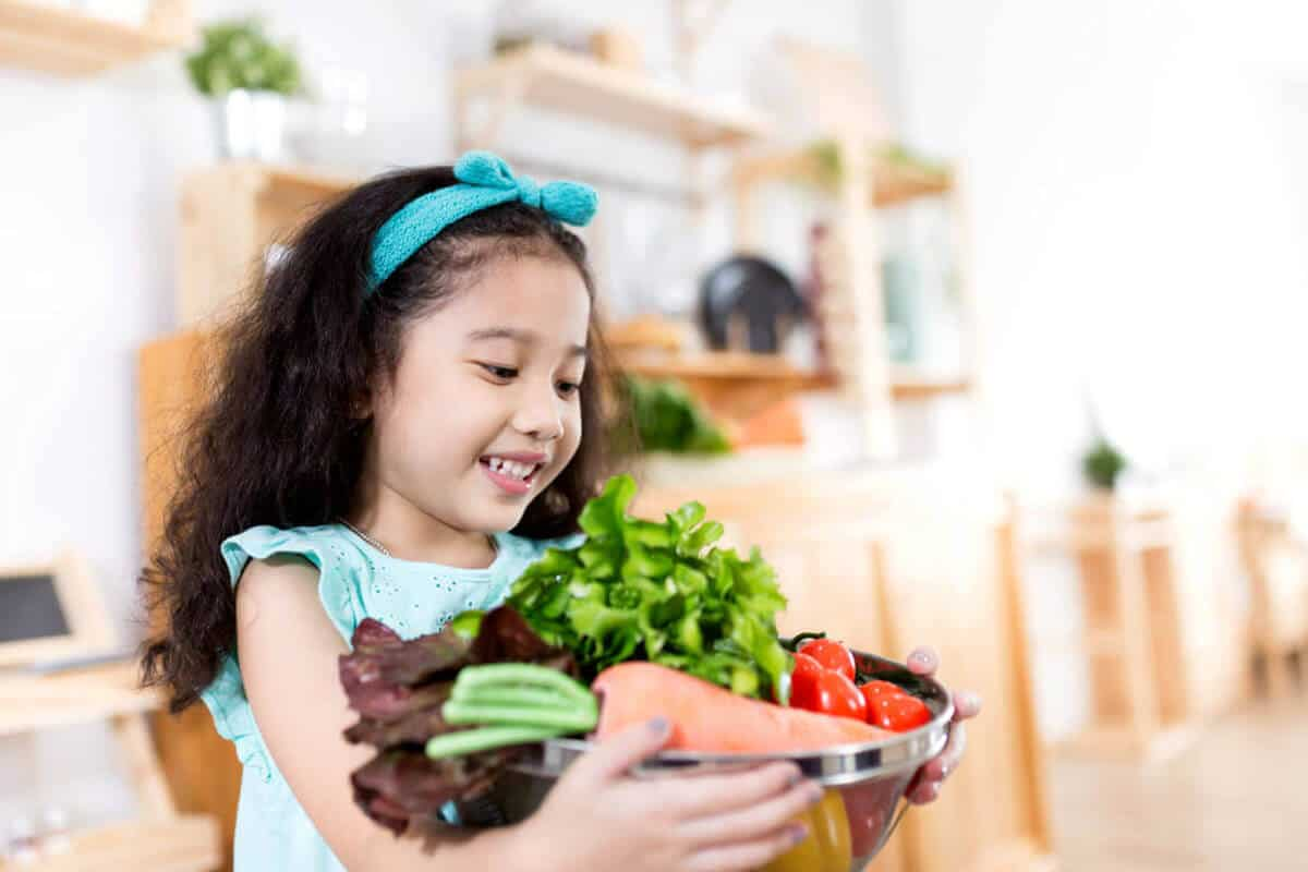 Young girl holding a bowl of vegetables and smiling.