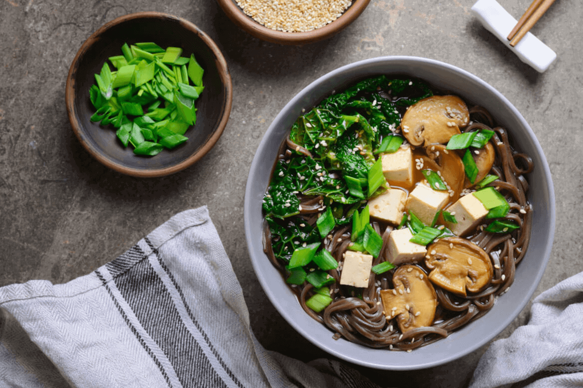 A bowl of Asian noodles with mushrooms, tofu, and greens on a grey backdrop.