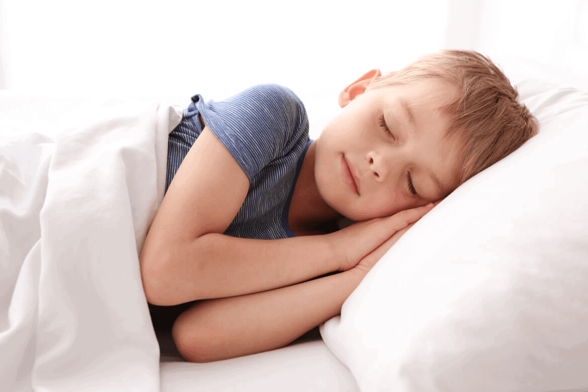 child sleeping on his bed