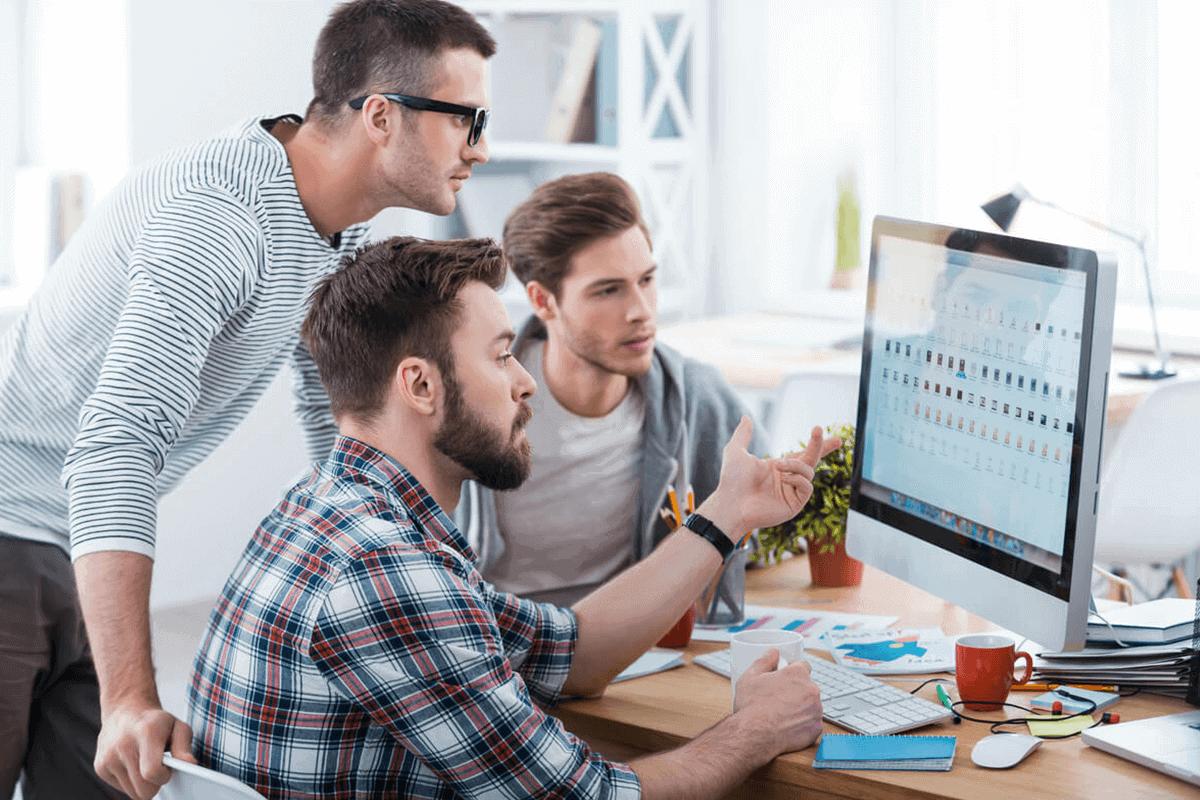 three people on a desktop, working