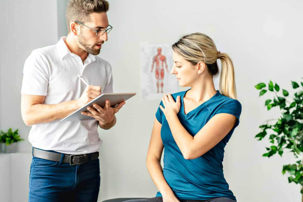 chiropractic taking notes and evaluating patient