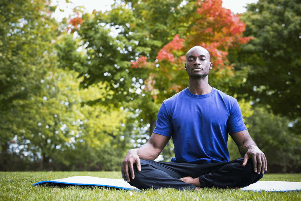 Man sitting cross-legged outdoors and meditating.