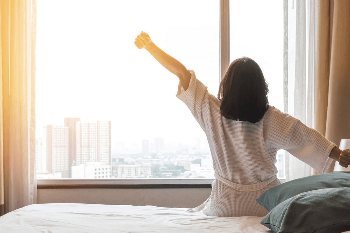Woman sitting on a bed stretching while looking out of the window.