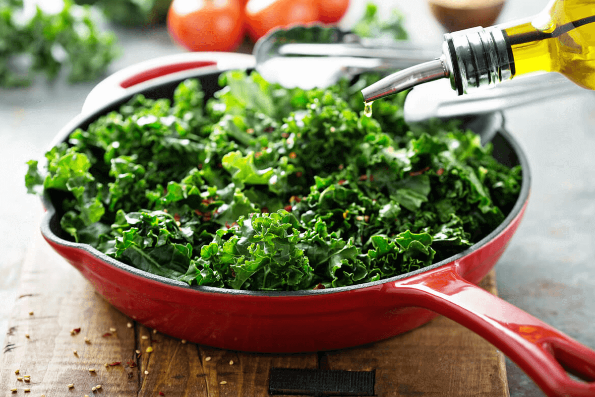kale in a pan with oil being poured on it